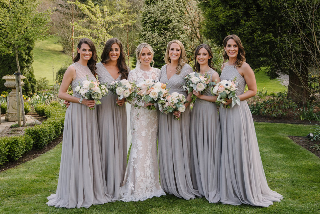 Wedding flowers at Crossbasket Castle - Emily with her five bridesmaids in the gardens