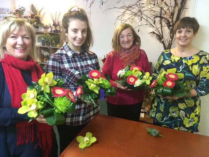 Glasgow flower arranging classes with Nicole Dalby. 4 ladies stand behind a work table holding their floral table decorations, smiling at the camera